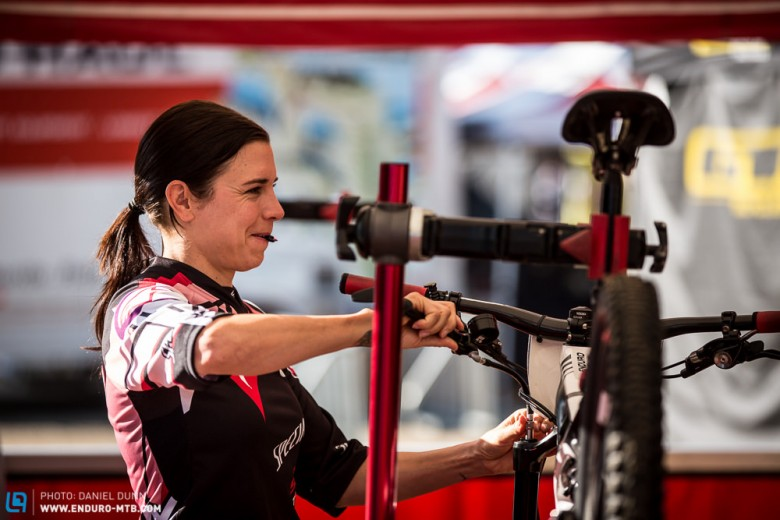 When the pressure in your fork needs adjusting, sometimes it's best to have a woman's touch. Anneke Beerten is trying to not smile with the valve cap in between her lips.