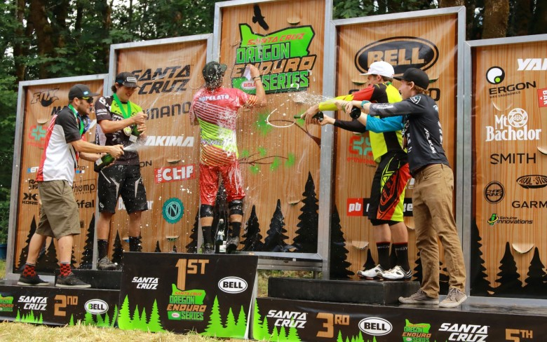 The pro men sneak up on the 1rst place rider Mitch Ropelato and drench him with some victory champane.